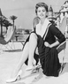 1955: Italian actress Sophia Loren sits outdoors in a butterfly chair on the beach at Cannes, wearin